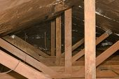 foto of attic  - Dark attic rafters with solar barrier in a house - JPG