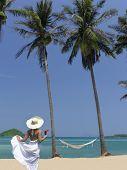 Постер, плакат: Женщина в шляпе и белое платье на пляже с коктейль