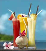 three fresh juices and coconut on the beach on the table