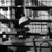 A Table With A Retro Lamp In A Quiet Library. Monochrome Image Reflecting The Silence In An Empty Li poster