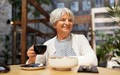 old age, leisure, retirement and people concept - happy senior woman drinking coffee at street cafe poster