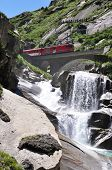 Alpine express passing bridge at St. Gotthard Pass in Switzerland