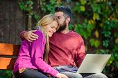 Couple With Laptop Sit Bench In Park Nature Background. Family Surfing Internet For Interesting Cont poster