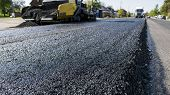 Worker Operating Asphalt Paver Machine During Road Construction And Repairing Works. A Paver Finishe poster