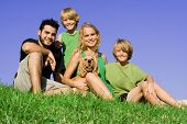 image of family fun  - happy smiling family group with pet dog outdoors - JPG