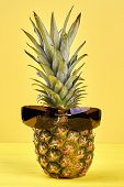 Fresh Hawaiian Ananas In Sunglasses. Delicious Tropical Fruit On Yellow Background. Food And Summer  poster