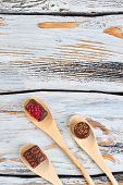 Three Chocolate Candies In Wooden Spoons. Traditional Wooden Spoons With Chocolate Sweets On Wooden  poster