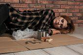 Poor Homeless Woman Lying On Floor Near Brick Wall poster