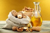 stock photo of walnut  - Walnut oil in bottle and nuts on a wooden table - JPG