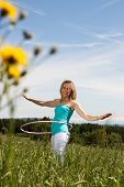 picture of hulahoop  - Young woman standing on a lawn and trained with hula hoops - JPG