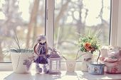 image of decoupage  - against the window of flowers in pots on the windowsill is a doll - JPG