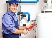 picture of pipe wrench  - Smiling technician repairing an hot - JPG