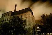 image of wiccan  - Old urban industrial building with dramatic night sky and clouds - JPG