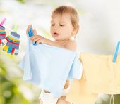 bright picture of adorable baby doing laundry