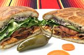 stock photo of jalapeno peppers  - Closeup of halved Mexican torta sandwich with toasted bun and jalapeno pepper on plate over colorful tablecloth - JPG