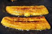 stock photo of plantain  - Closeup of crisp yellow sliced plantain bananas frying in pan with hot oil - JPG
