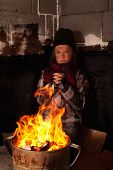 stock photo of beggars  - Poor beggar child warming up at the fire made in tin pot  - JPG