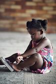 Young african girl tying shoelace and putting shoot on foot in rural setting