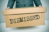 image of unemployed people  - a businessman carrying a box with the word dismissed written in it - JPG