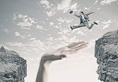 stock photo of overcoming obstacles  - Young successful businessman jumping over gap - JPG