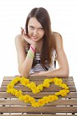 picture of 15 year old  - One girl brunette teen Caucasian 15 years old sitting at a table on which is lined with heart valentines yellow flowers of dandelion isolated on white background image - JPG