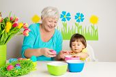 image of child development  - Happy grandmom and grandson color eggs for Easter at home