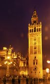stock photo of christopher columbus  - Giralda Spire Bell Tower Seville Cathedral Rainy Night Car Trails Seville Andalusia Spain - JPG