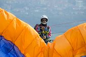 image of lifting-off  - paraglider pilot preparing for lift-off in reverse launch style. 