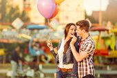 stock photo of candy cotton  - Young romantic man in love feeding his girlfriend with cotton candy - JPG