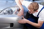 pic of scratch  - A man trying to fix a scratch on a car body  - JPG