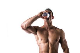 stock photo of blender  - Muscular shirtless male bodybuilder drinking protein shake from blender - JPG
