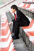 stock photo of bleachers  - Young man in black suit sitting on the audience bleachers - JPG
