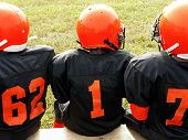 stock photo of sitting a bench  - photo of little league football players sitting on a sidelines bench awaiting their turn to play - JPG