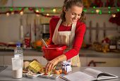 picture of christmas cookie  - Happy young housewife making christmas cookies in kitchen - JPG