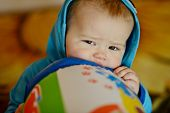 stock photo of love bite  - baby biting toy in soft selective focus - JPG