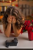 stock photo of sad christmas  - Stressed young housewife near phone in christmas decorated kitchen  - JPG