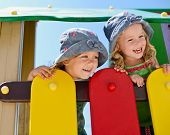 picture of identical twin girls  - happy toddler girls playing on the playground - JPG