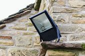 foto of flood-lights  - Home security light mounted on the corner of a rural stone cottage - JPG