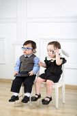 picture of lurex  - Two little kids in glasses sitting on white chairs - JPG