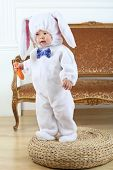 stock photo of bunny costume  - Little boy in costume bunny standing on pouf with carrot  - JPG