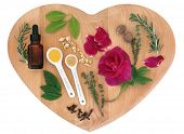 picture of wiccan  - Love potion ingredients on a heart shaped wooden board over white background - JPG
