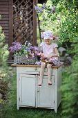 picture of dress-making  - cute happy little girl making lilacs flower wreath in sunny spring garden - JPG