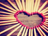 foto of combustion  -  matchsticks in the shape of a heart toned with a warm retro vintage instagram filter effect - JPG