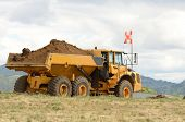 stock photo of big-rig  - Large dump tractor moving dirt and rocks for a airport runway extension project in Oregon