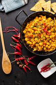 pic of curry chicken  - indian chicken curry with peas and chili pepper on pan - JPG