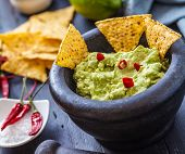 image of nachos  - black stone bowl with fresh guacamole and nachos for dip - JPG
