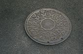 picture of metal grate  - Metal circle of drain water on the floor of pavement - JPG