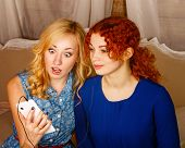 pic of sisters  - Two sisters a blonde and a redhead listening to music on headphones - JPG