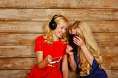 picture of sisters  - Two sisters blonde listening to music on headphones - JPG