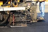 stock photo of paving  - Asphalt paving machine laying down a fresh layer of paving on a new road interchange project - JPG